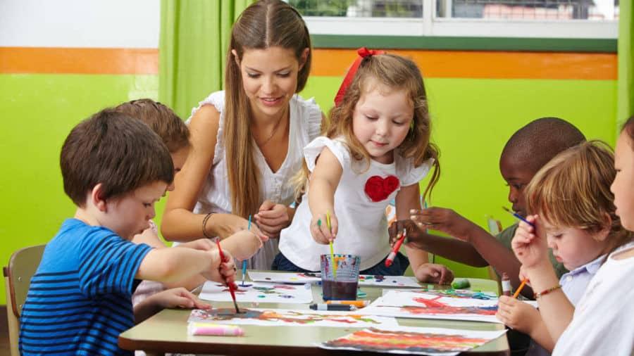 Dzieci malują farbami z wychowawczynią w przedszkolu