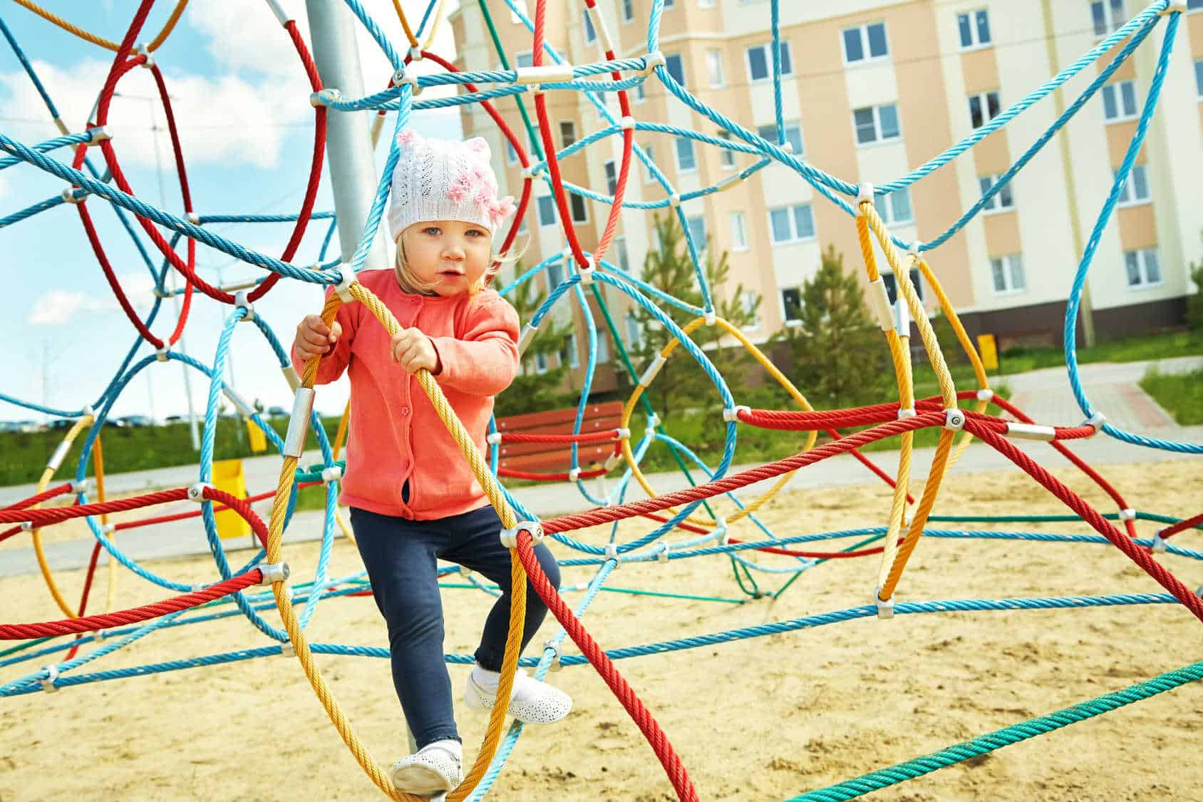 Dziewczynka wspina się na placu zabaw.
