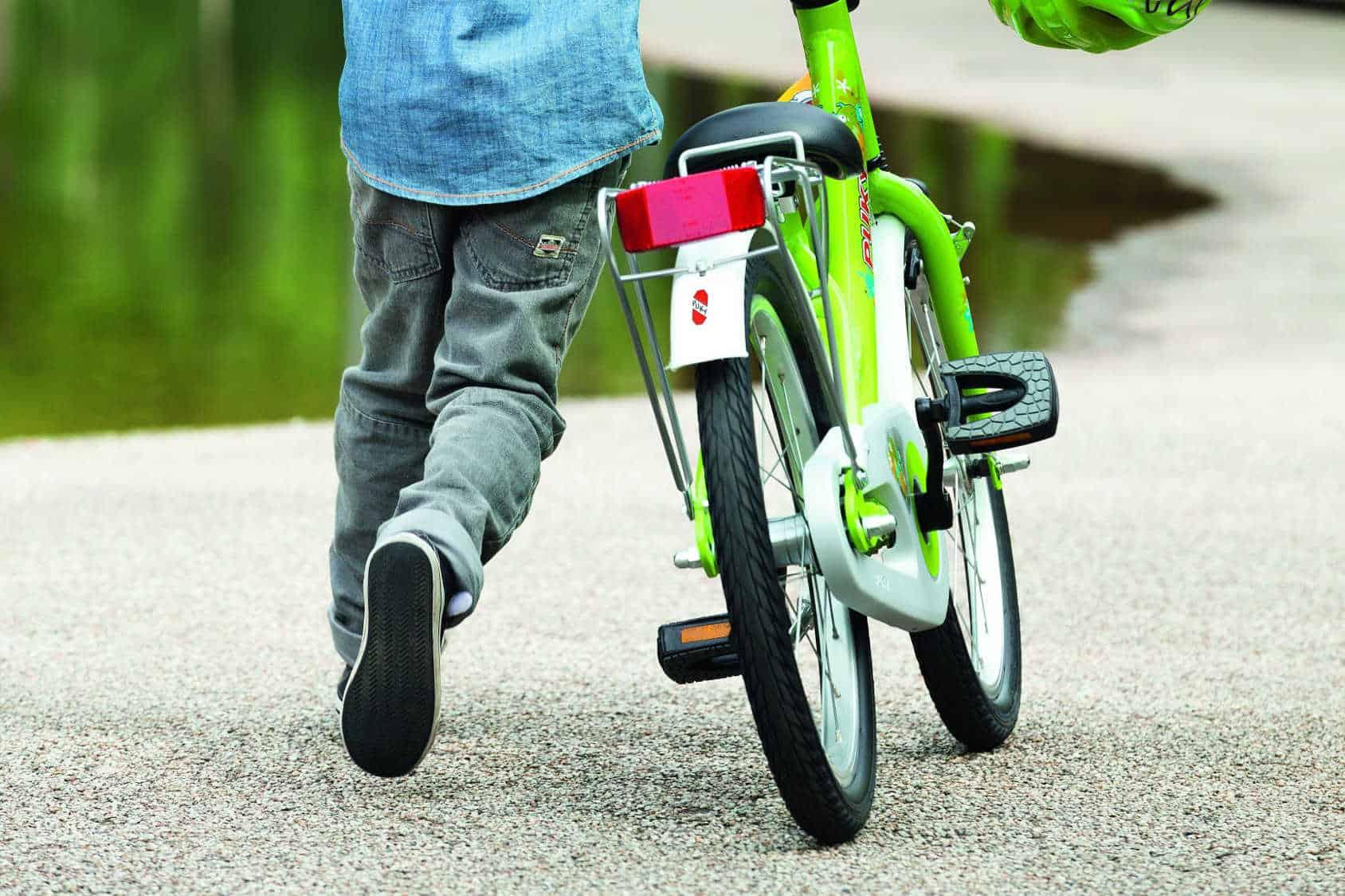 Chłopiec chodzi obok roweru