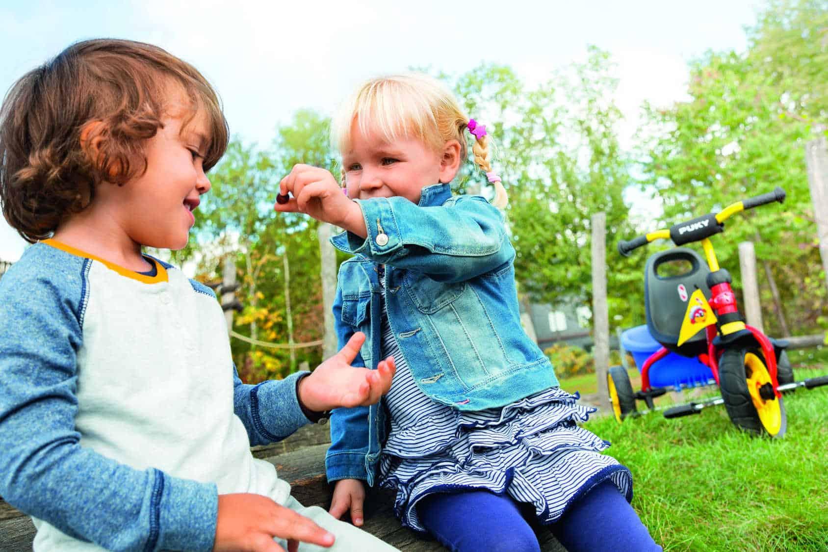 Chłopczyk i dziewczynka bawią się obok rowerku.